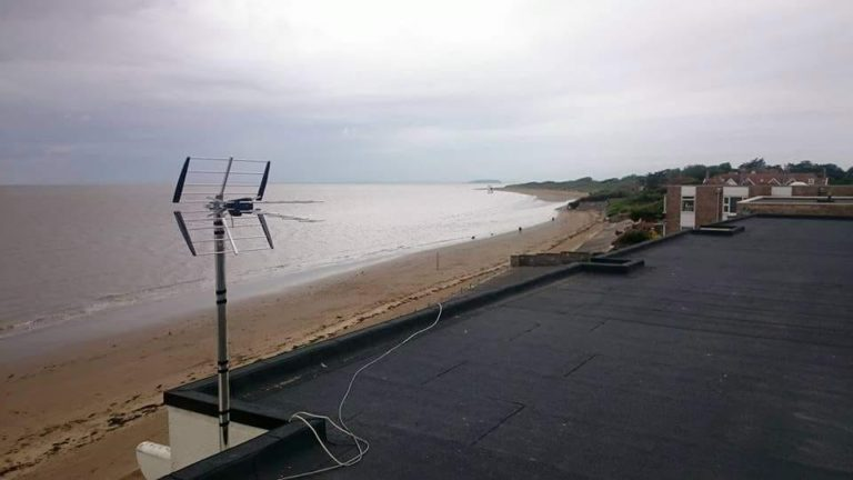 A TV antenna overlooking a cloudy beach on a rooftop